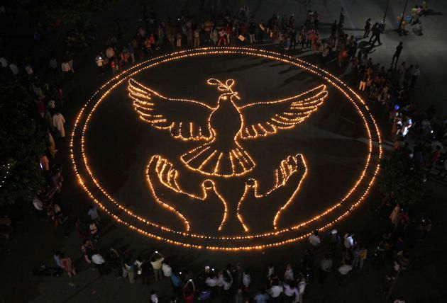 Eople Light Lamps As They Make A Formation Of A Peace Symbol On The