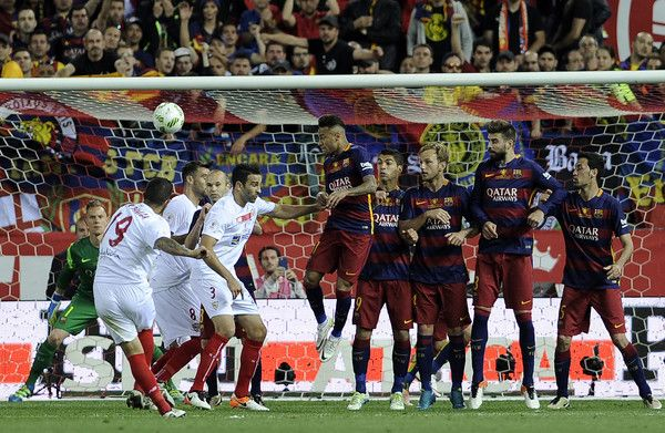 """Sevilla's Argentinian midfielder Ever Banega (L) shoots the ball during the Spanish """"Copa del Rey"""" (King's Cup) final match FC Barcelona vs…"""