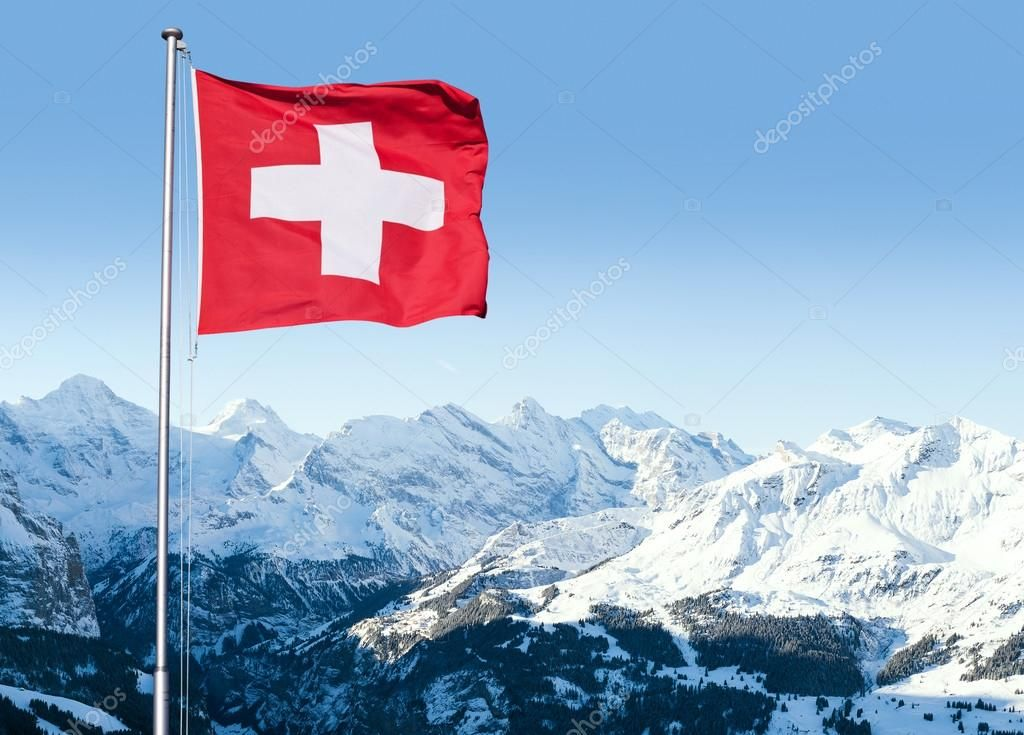 Swiss Flag Flying Over Alpine Scenery Royalty Free Stock Photos