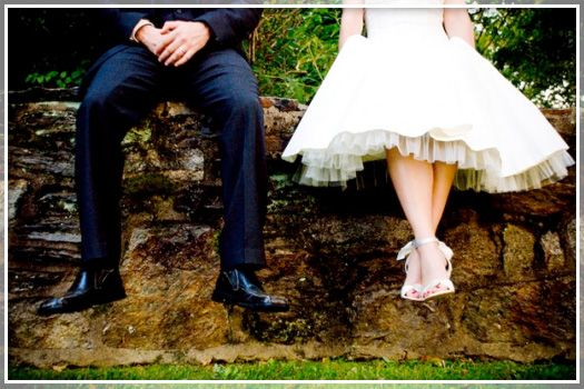 Cute shot of just  the lower half of the body, shoes, sitting on a wall...