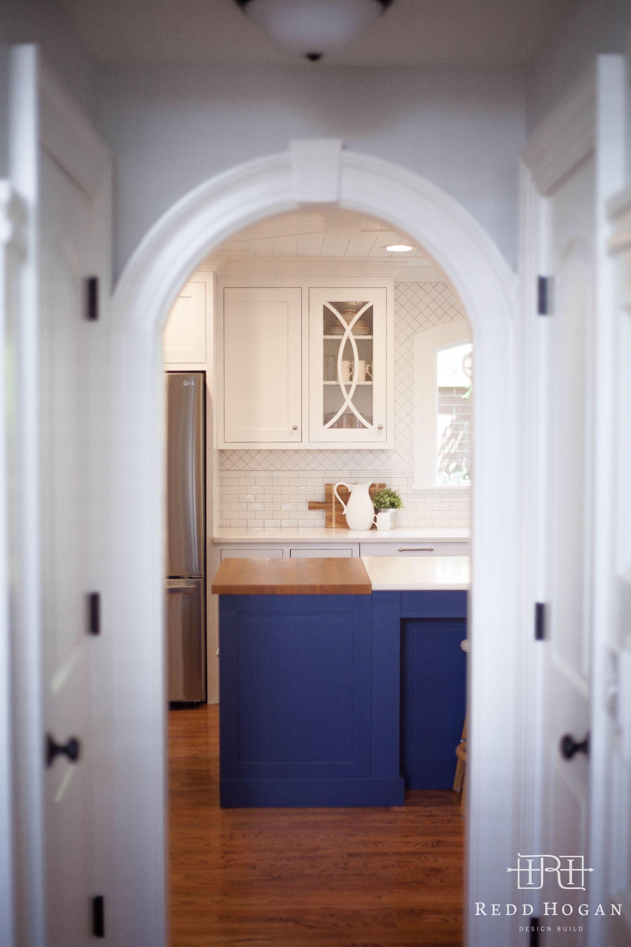 REDD HOGAN DESIGN BUILD | Holladay::Main Floor Remodel  Curved cabinet door detail, arched pass through, keystone, trim, blue island, butcher block, caesarstone, quartz countertop, hardwood, door casing, arched door