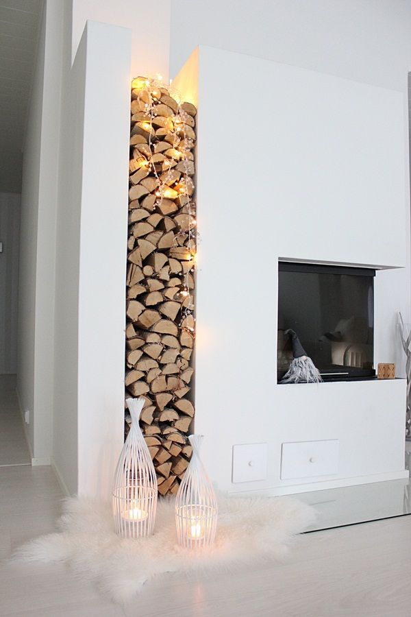 modern fire place, stacked chopped wood, Christmas tree lights ...