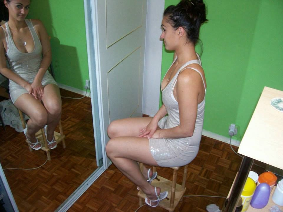 Brunette girl sitting in front of mirror-----hair style------short gown------reflection