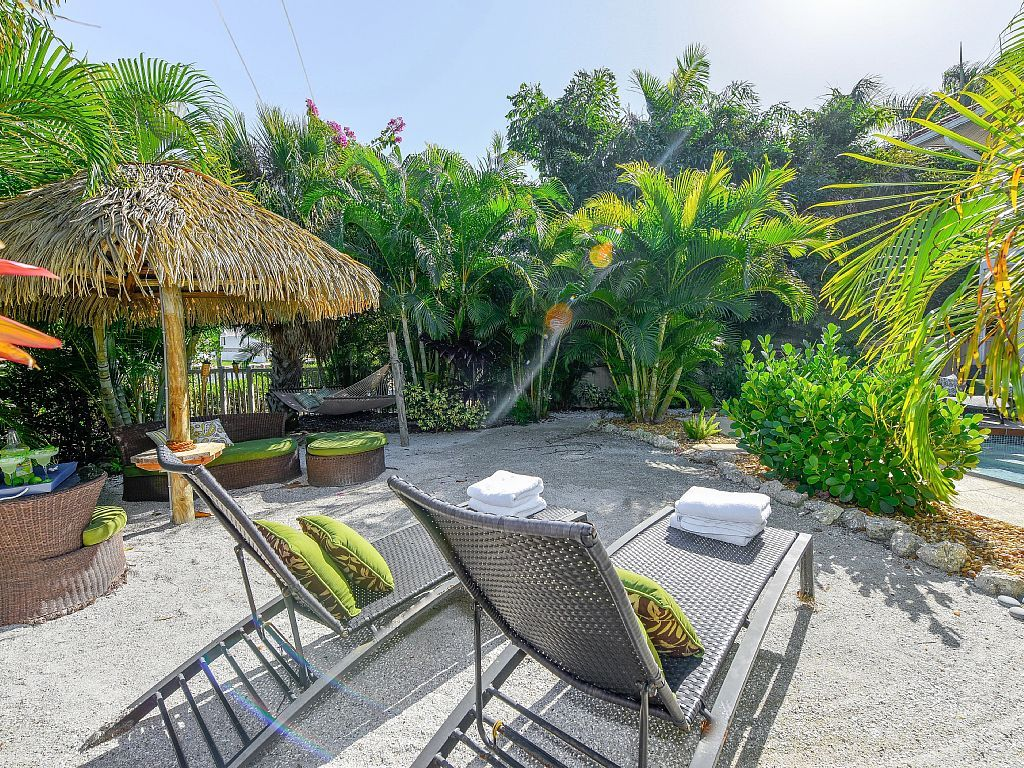 the sunny backyard beach tiki hut and hammock are waiting for you