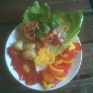 Pan fried Wild Alaskan Salmon cooked in fresh ginger,basil,olive oil,soy sauce,on a bed of lettuce leaves.Jersey Royal new potatoes spring onions and an assortment of peppers and tomatoes.