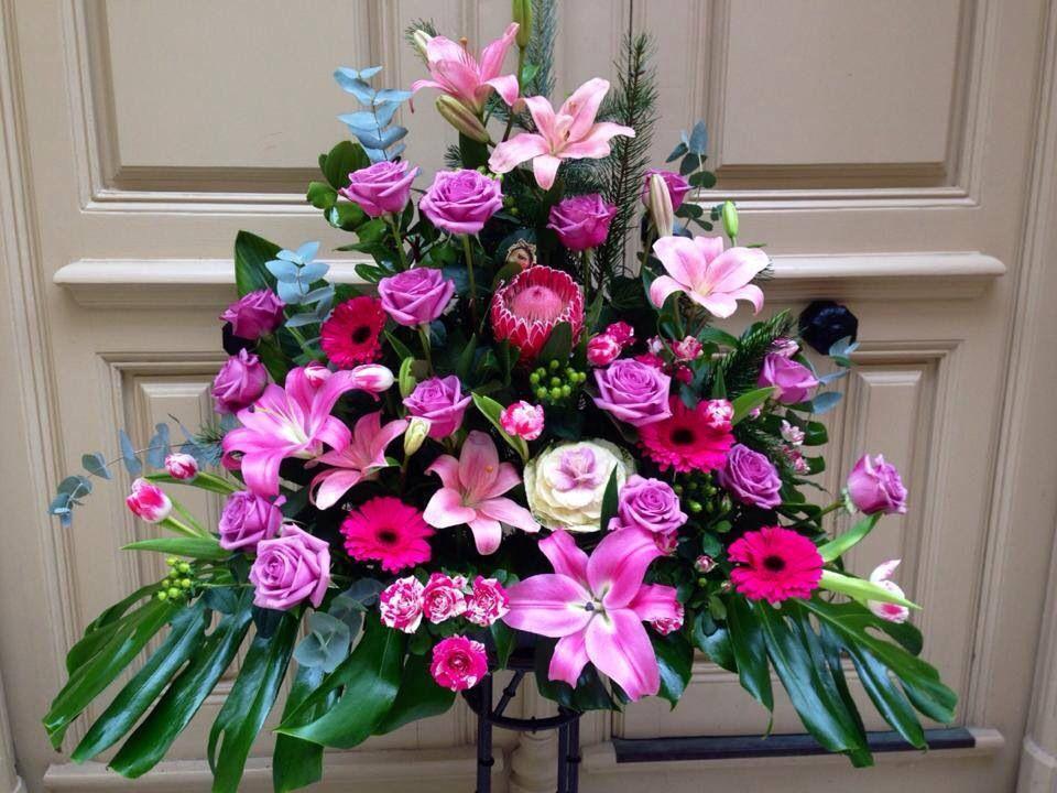 Centro con rosas, proteas, liliums, rosas ramificadas, tulipanes, hypericum y verdes tipo monstera, eucalipto y pino
