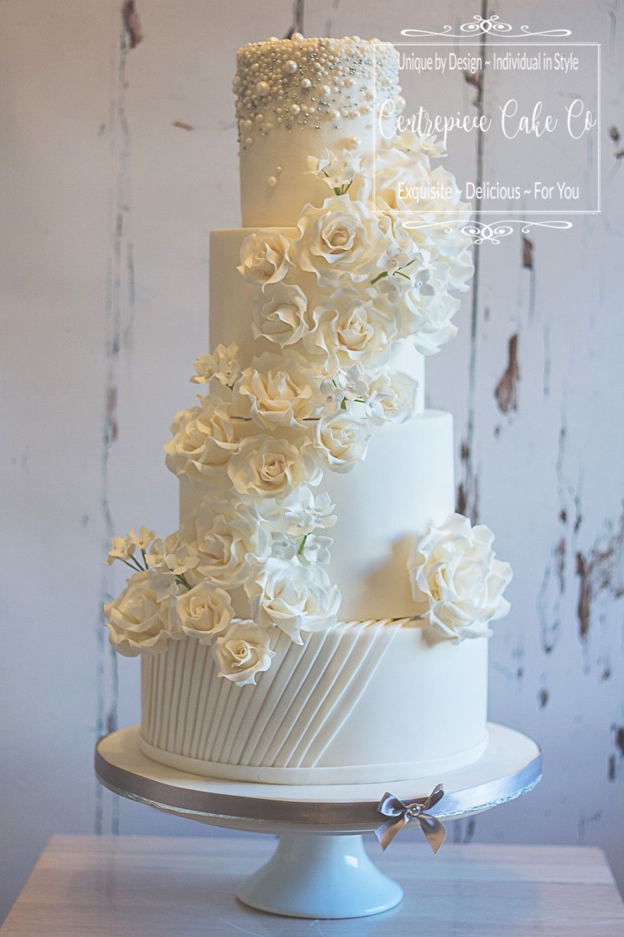 White wedding cake with silver u pearl touches white sugar flowers