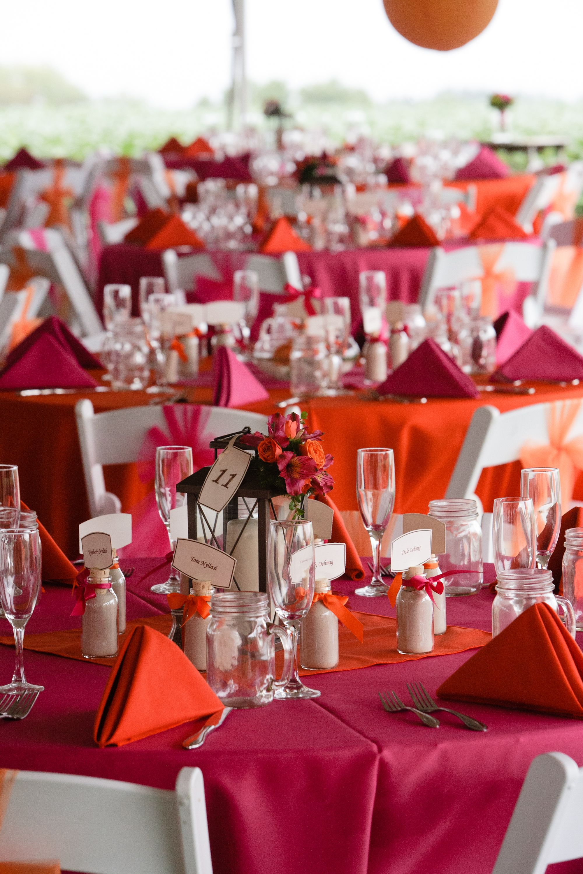 Hot Pink And Orange Alternating Linens Napkins With White Resin Padded Folding Chairs