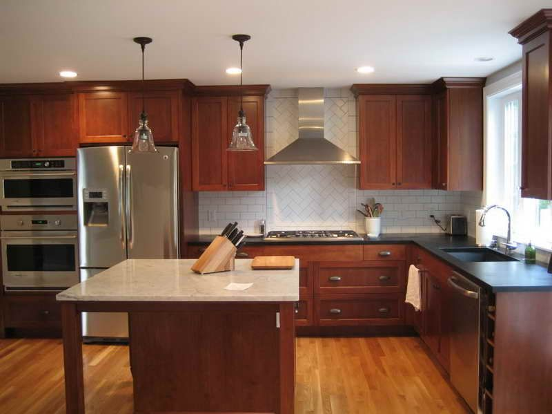 cherry cabinetry brightened by subway tile wall and light ...