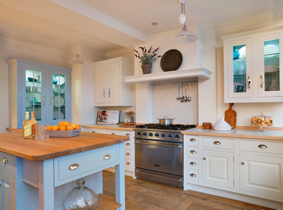 white kitchen with pale blue cabinets and wood countertops | white