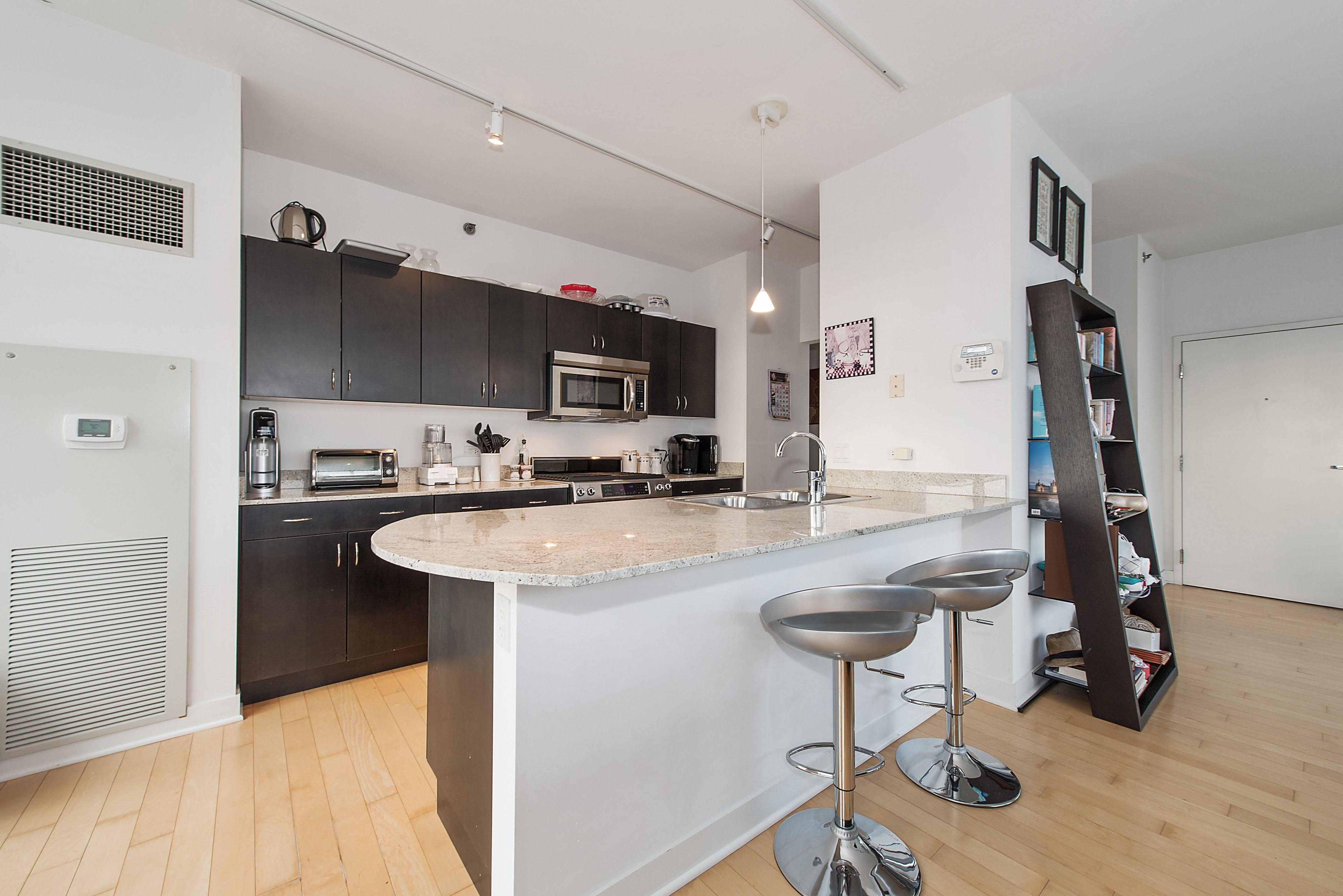 Modern kitchen with hardwood floors black cabinets pendant