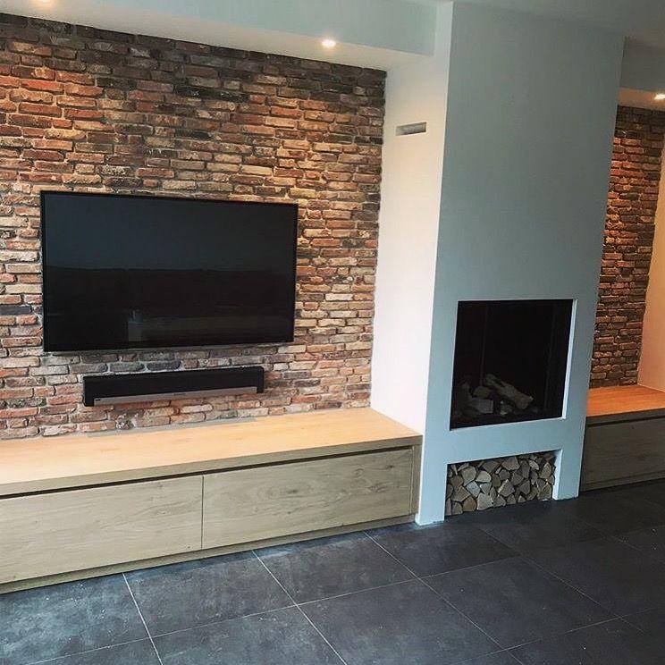 Bakstenen muur met gas haard en houten wandmeubel (woonkamer ...