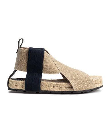 STUDIO COLLECTION. Et par sandaler med brede, korslagte remmer av elastikk og lav platåsåle av jute. Sandalene har kontrastfarget elastikk i sidene og skinnbånd ved hælene. Platå 2,5 cm. Gummisåler.