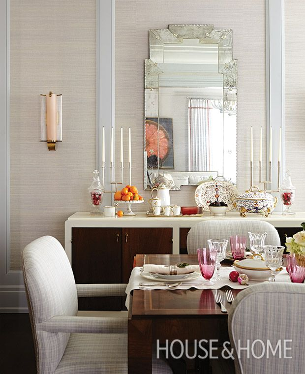 A cake plate toppling with clementines adds Christmas spirit to this dining room, while fuchsia glassware on the tablescape and console are a subtle nod to the holidays.   Photographer: Angus Fergusson   Designer: Silvana D'Addazio