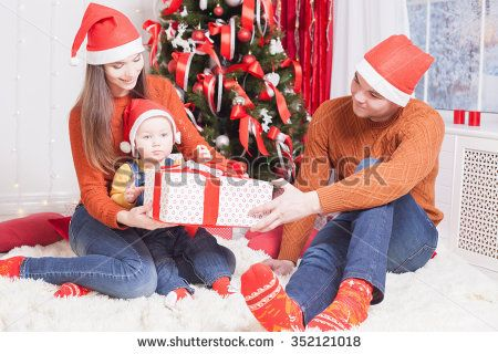 Happy family at Christmas eve sitting together near decorated tree at living room, home. Father giving gift to baby and mother looking at child. New Year.