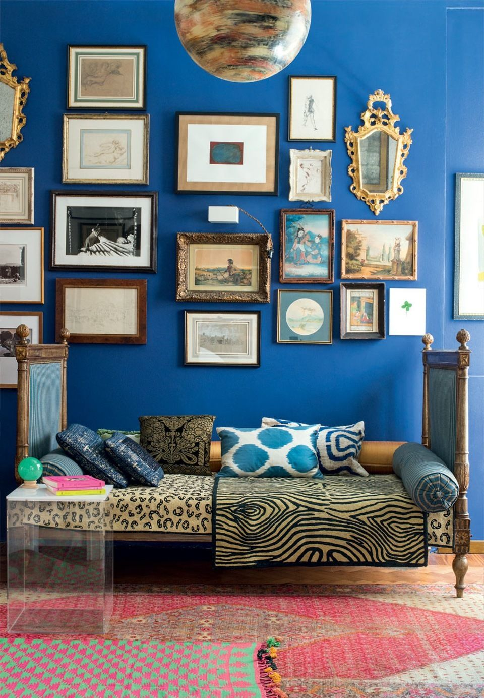 Antique gallery wall with a blue wall background featuring artworks, drawings and photographs between french mirrors.