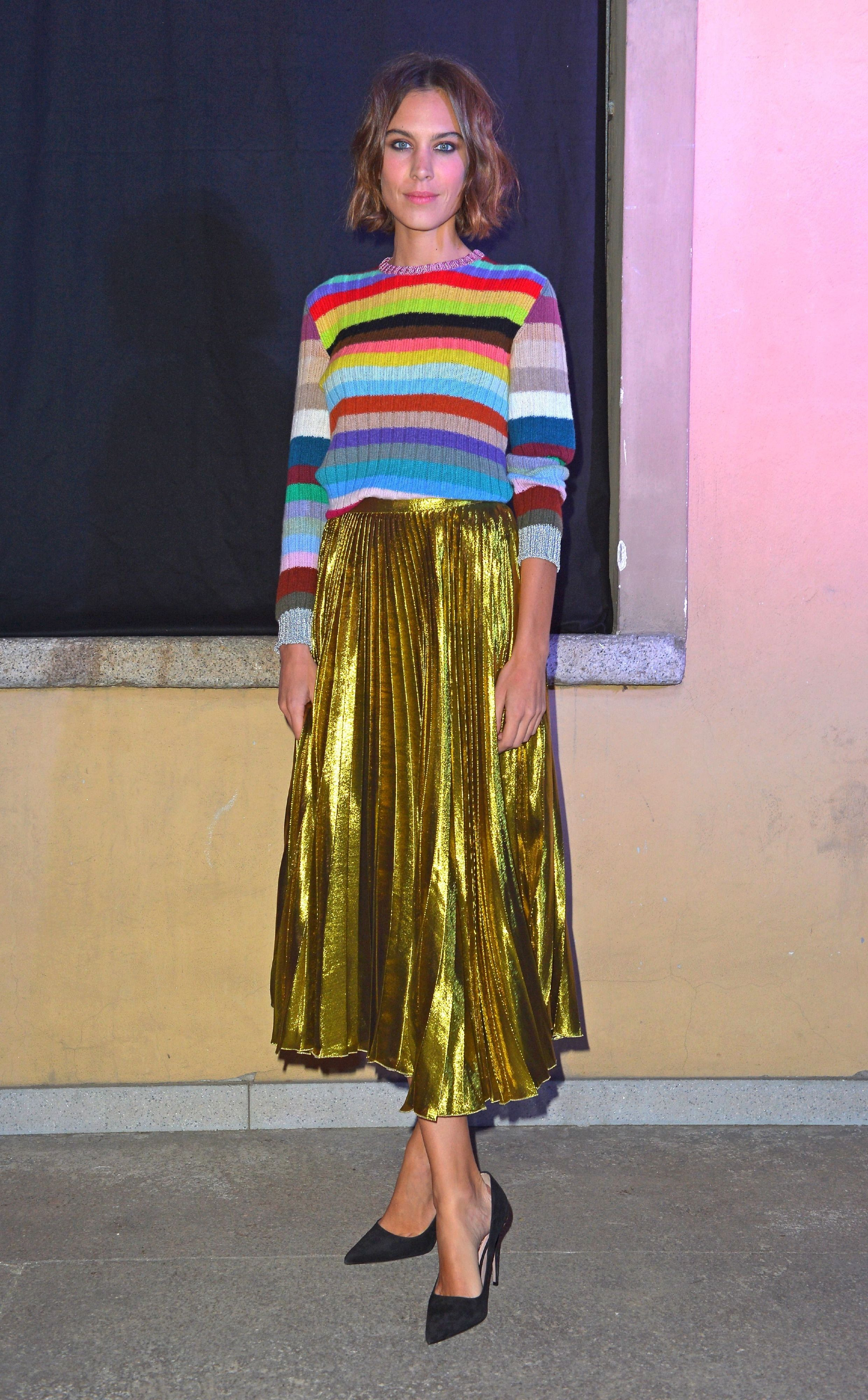 Alexa Chung wears a rainbow stripped knit with a metallic pleated midi skirt and black pumps.