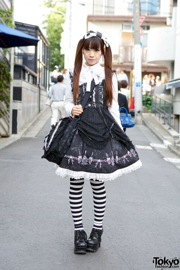 Alumi's top and skirt are from Frill, and they both have ruffles and lace details. Her lace heart bag is from Hangry & Angry. Her heeled oxfords are from Yosuke, and she's wearing them with striped tights. She told us her katyusha (head piece) is from Hn+nois.