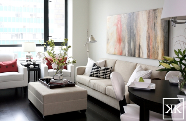 Kerrisdale Design  Chic city living room design with ivory linen modern sofa storage ottoman white curvy rooms oatmeal