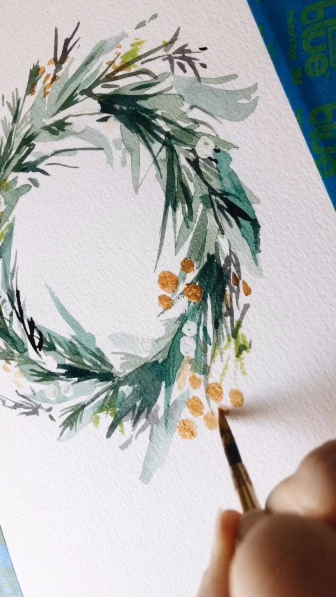 Adding gold details to this holiday wreath by @leahbischstudio #christmas #holidaydecor #watercolor #gouache #painting #workinprogress