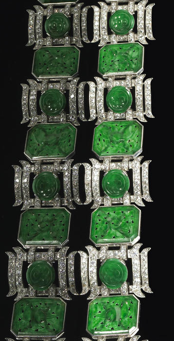 A jadeite jade, diamond and platinum bracelet the link bracelet featuring floral and animal carved jadeite plaques, alternating with links of circular carvings within a stylized pagoda motif, set with old European-cut diamonds; estimated total diamond weight: 11.60 carats; length: 7 3/4in.