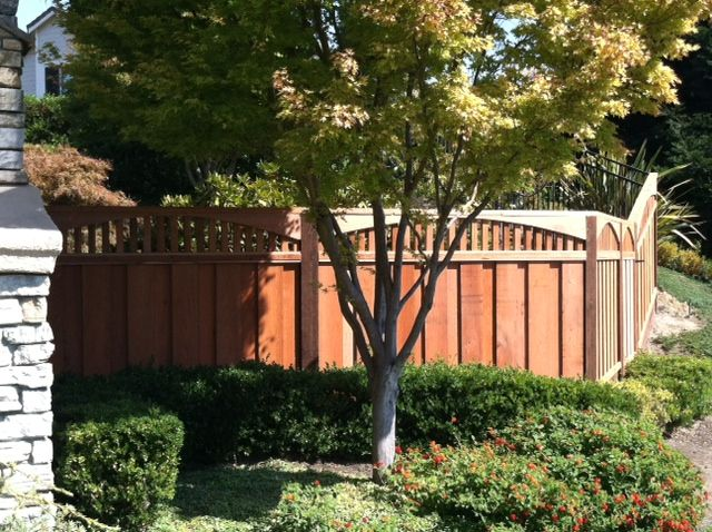 Gorgeous redwood fence with arched piano key lattice.