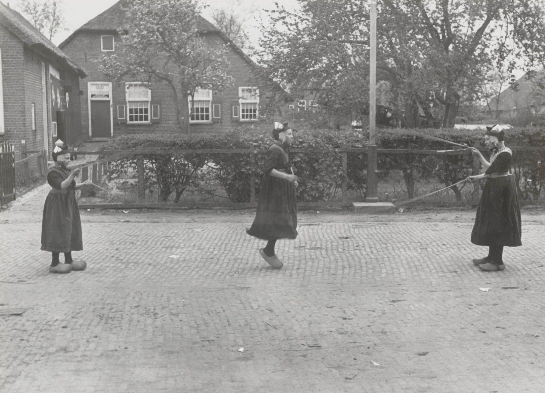 Drie meisjes in Staphorster streekdracht zijn aan het touwtje springen met twee touwen tegelijk. 1944 #Overijssel #Staphorst