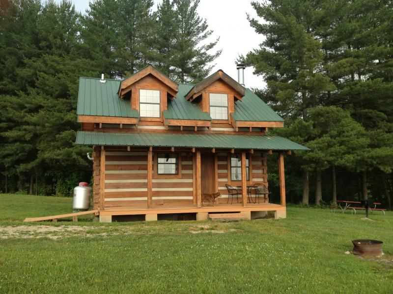 This two story cabin has a full size kitchen and a full size bath. One private bedroom downstairs and the second story is full of queen, full size and twin beds. It has a big wood burning fireplace, dining table, and couch. It has electric, city water and sewer and air conditioning and heat. #trees #grass #cabin