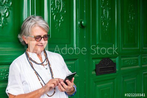 Photo of Senior kvinne med briller og grått hår som står og bruker mobiltelefonen. Bak henne en stor og grønn tredør med postkassen. – Kjøp dette arkivet og utforske lignende bilder på Adobe Stock