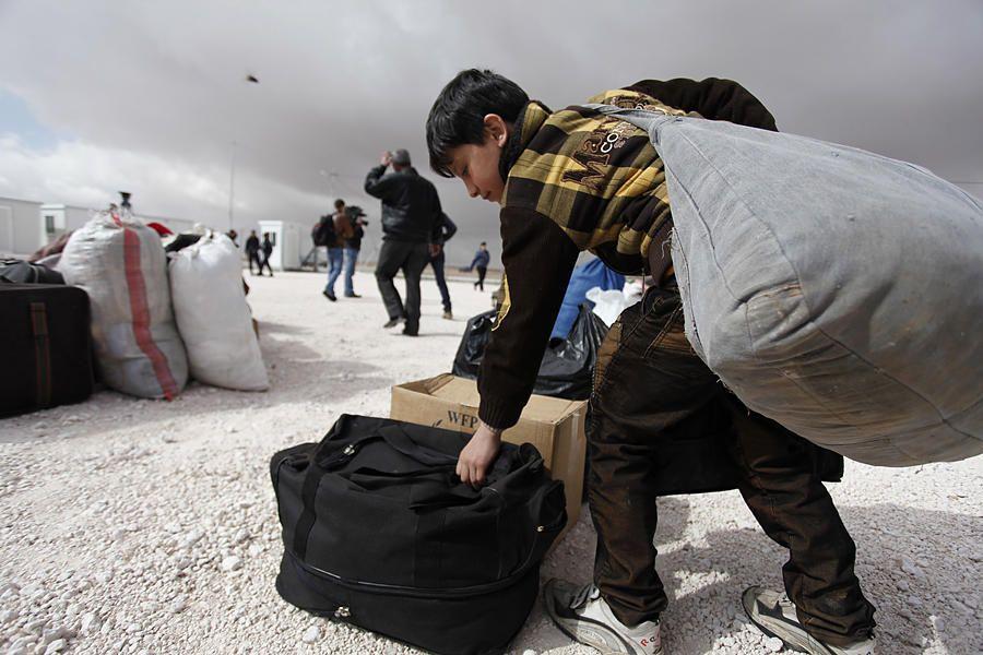 A newly-arrived Syrian refugee boy carries his familys belongings to the new Jordanian Emirati refugee camp, Mrajeeb al-Fhood, in Zarqa, Jordan.