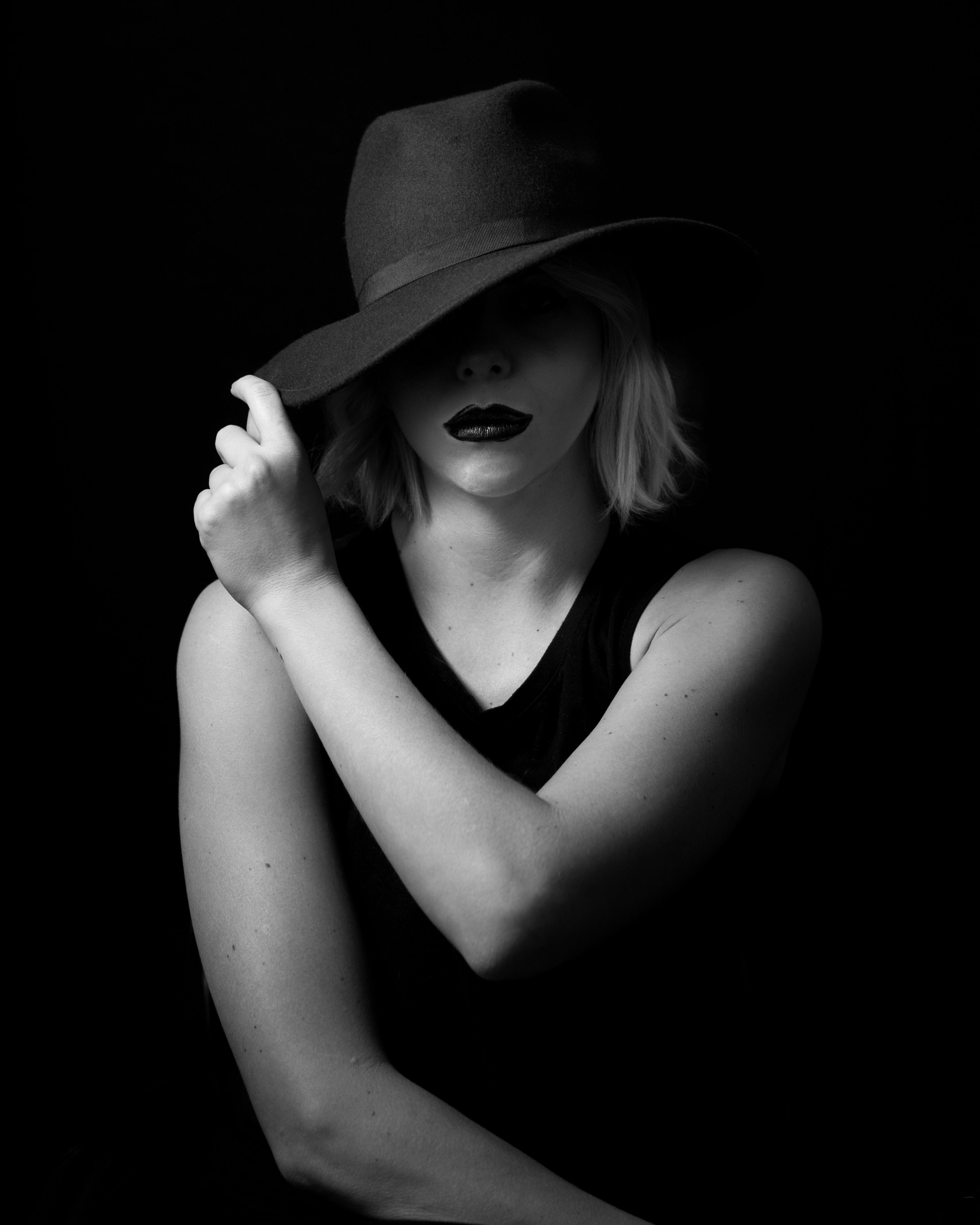 High contrast black and white female portrait woman with hat face partially obscured by shadow