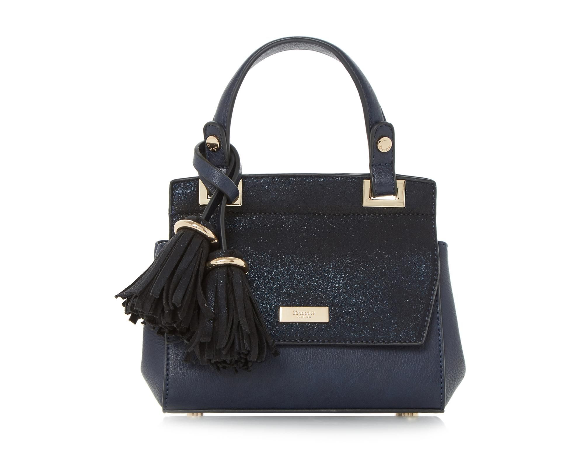 Go big on style and mini in size with this coveted micro bag. Featuring a flap over front with Dune branded hardware and top handle. Complete with an optional shoulder strap and oversized tassels.