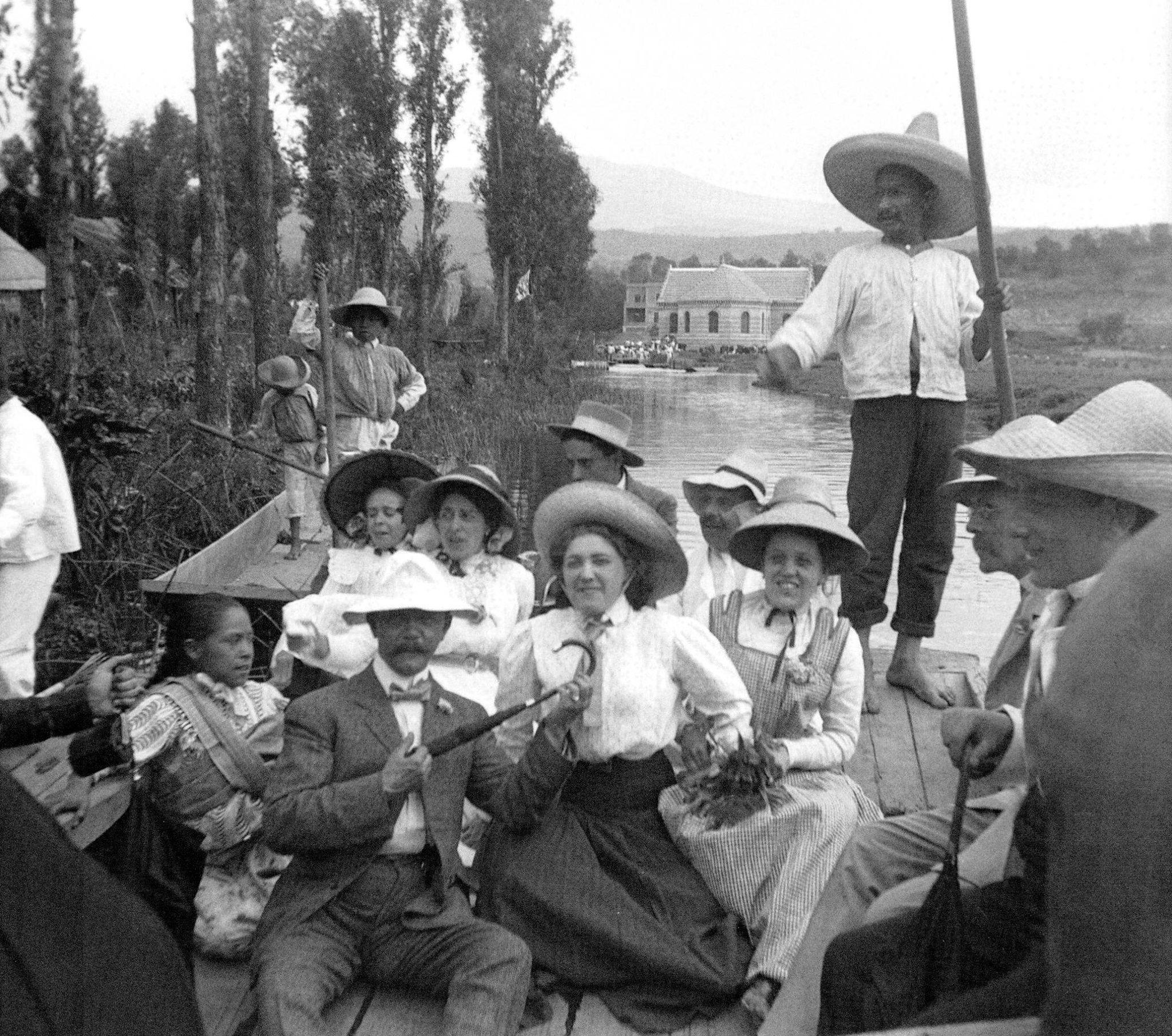 Un paseo en trajinera por los canales de Xochimilco en 1910. Al fondo se encuentra la casa de bombas de dicha localidad, que había sido construida poco antes como parte del sistema hidráulico porfiriano que llevó el agua desde esta zona hasta la Ciudad de México. El inmueble aún existe en la calle de Zacapa, cerca del embarcadero de Nativitas.