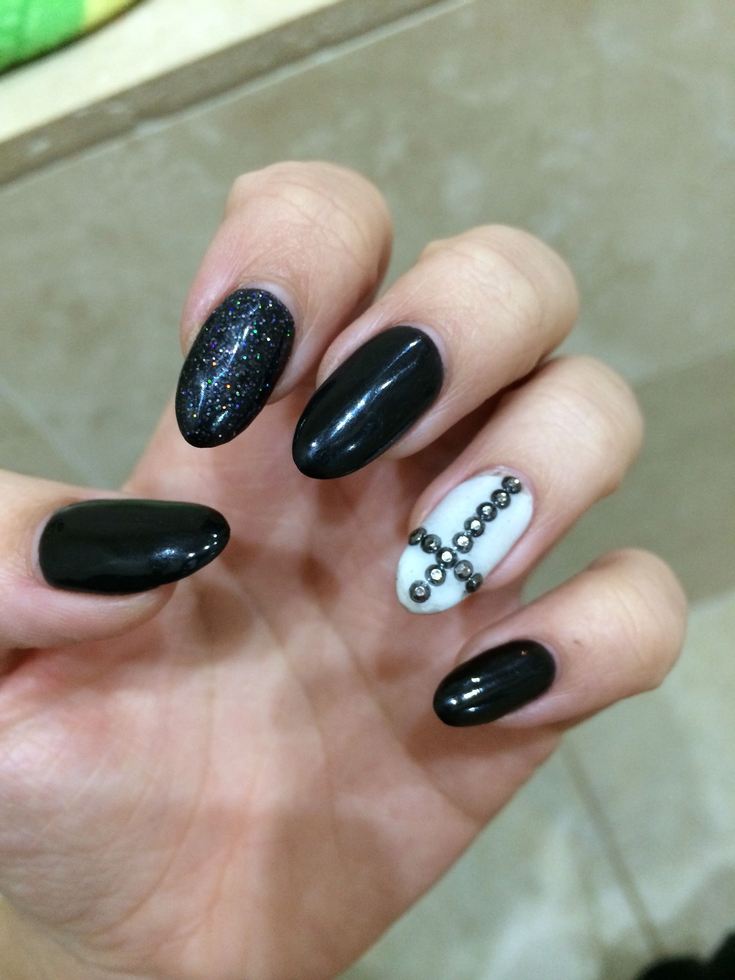 Black pointed nails, one glittery & one white with a silver studded ...