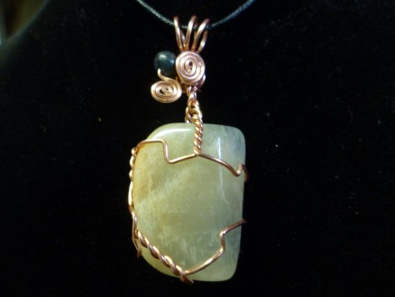 This is a Moonstone with tarnish resistant copper wire with a Kyanite stone bead. The Necklace is about 2 inches from the base of the point to the top of the wire cord loop. Comes with cord and mesh bag to protect the necklace, to be worn as a necklace.