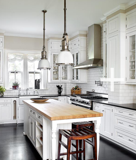 Crisp white kitchen design with glass front cabinets and black granite counter tops island butcher block also