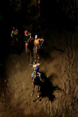 """Bruce Ely """"SUICIDE DROP""""   Before a plunge down 210 feet of a 60-degree slope covered with loose, wet sand, riders race their horses 120 yards toward the drop-off. They begin their near-blind descent at full gallop"""
