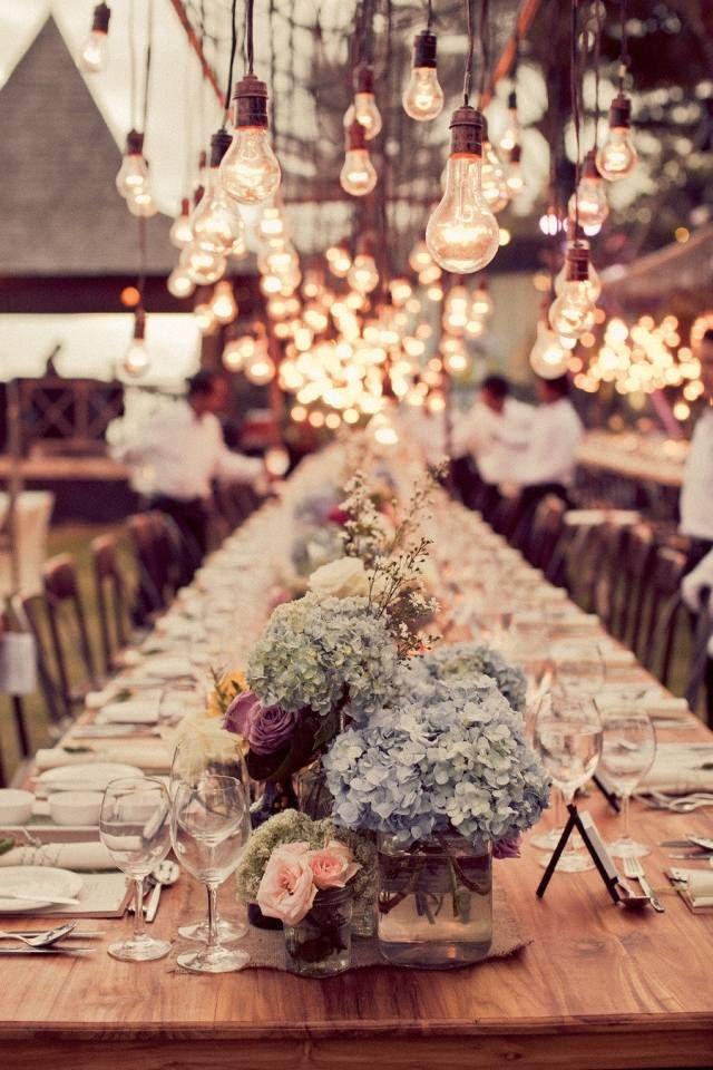 idées décoration mariage en plein air - suspensions ampoules et arrangements floraux sur la table en bois