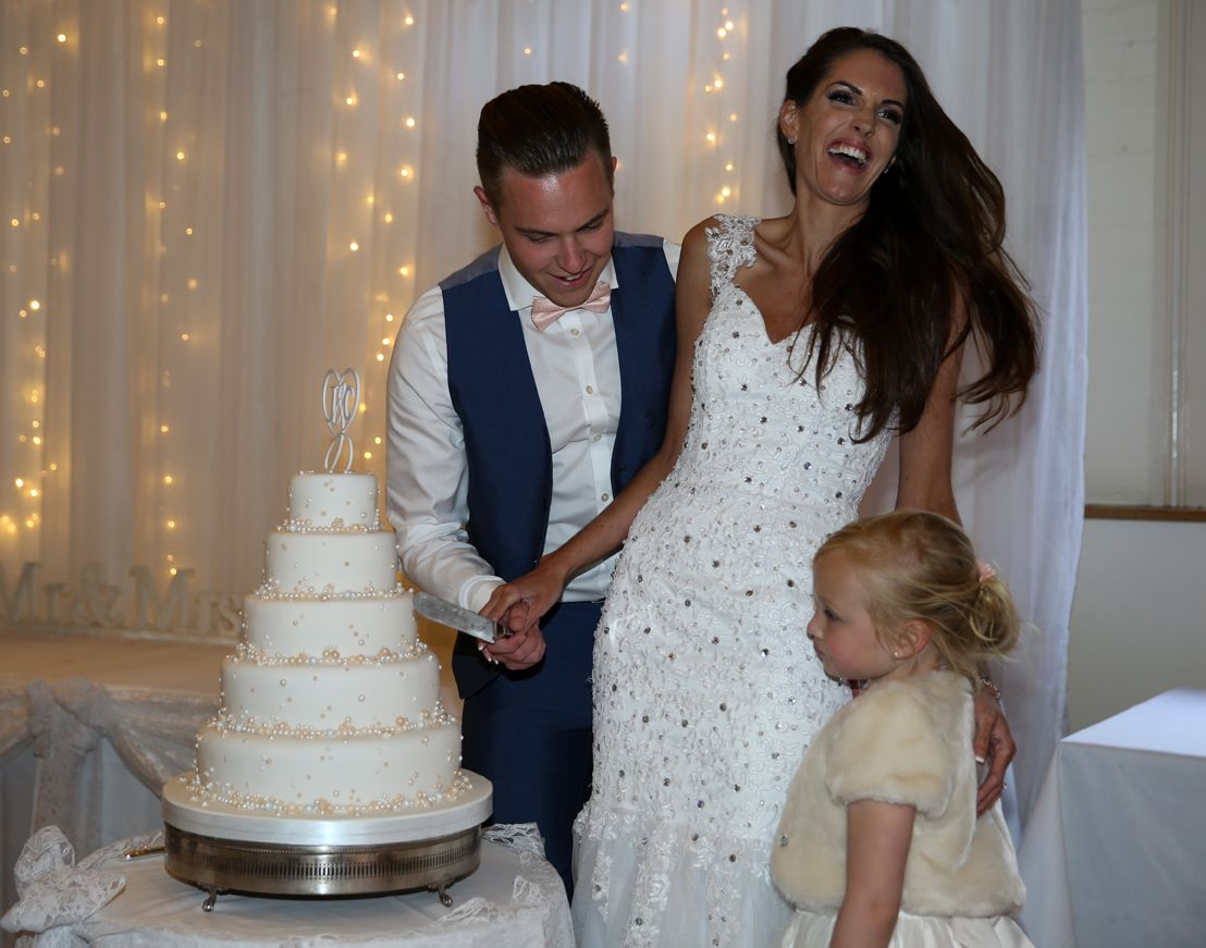 Laughing while cutting the cake.Bride & groom getting married outside in traditional style at Theobald's Park Hotel North London.