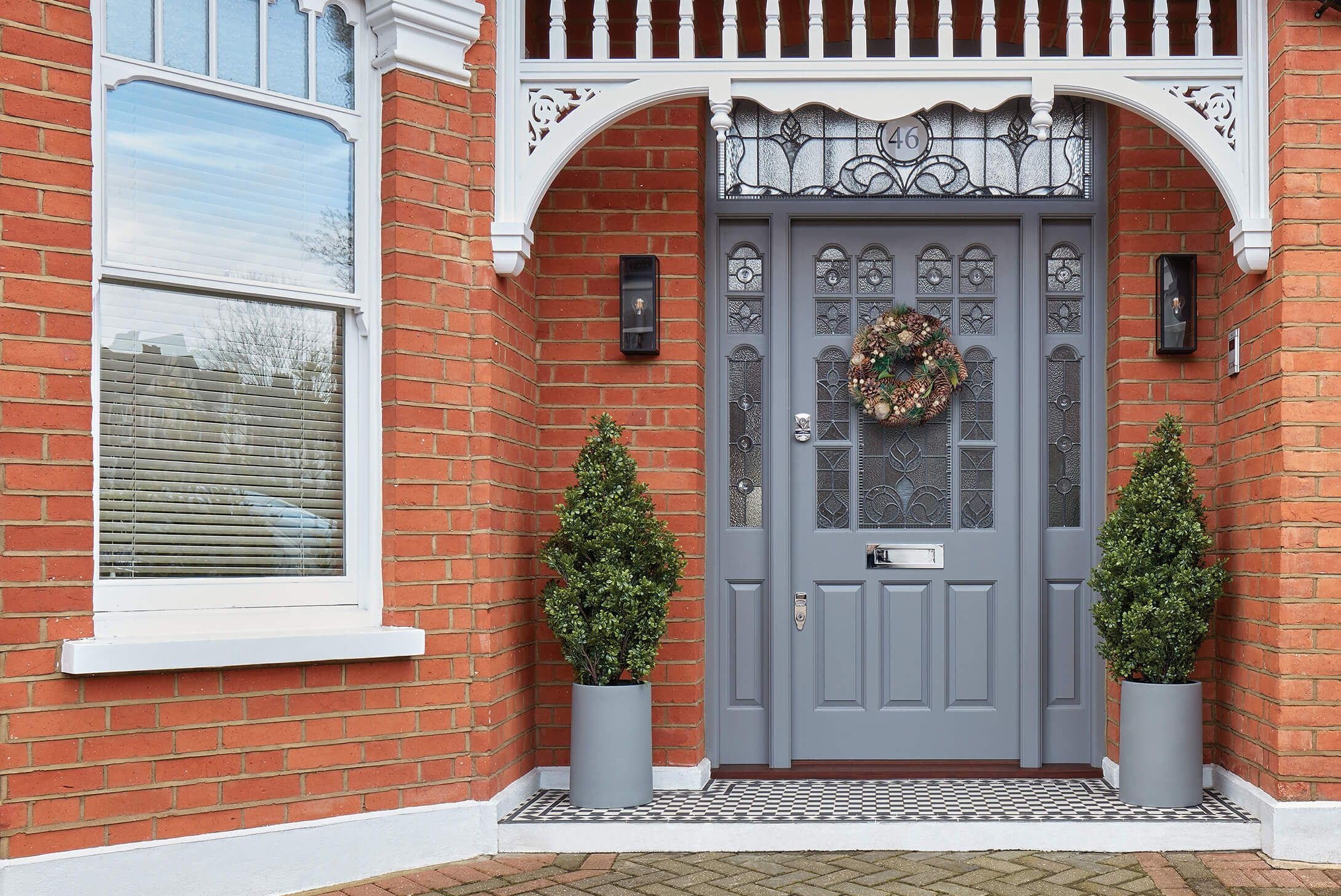 Gray Front Door With Glass Panels Transoms And Sidelights Porch Plants Red Brick Walls In 2020 Victorian Front Doors Traditional Front Doors Garage Door Styles