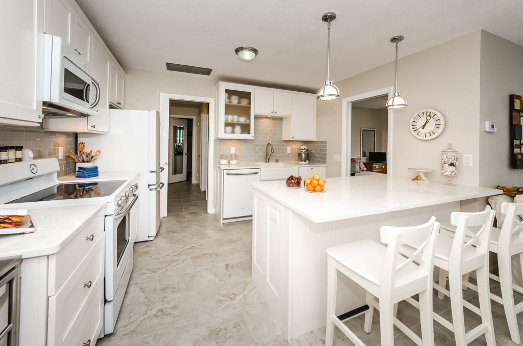 Strobel Design Build.  http://strobeldesignbuild.com/nari-award-winning-white-kitchen-remodel/ This transitional kitchen with a mid-century feel proves that kitchens don't have to be expansive to be stunning!