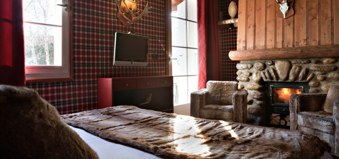 Cozy and warm fireside with in-room fireplace at Le Lodge Park a 4-star hotel, ski chalet chic in the French Alps in Megève (Haute Savoie)
