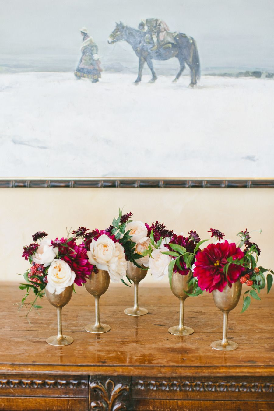 Floral arrangements in wine goblets. Photo by One Love Photography (via Style Me Pretty).