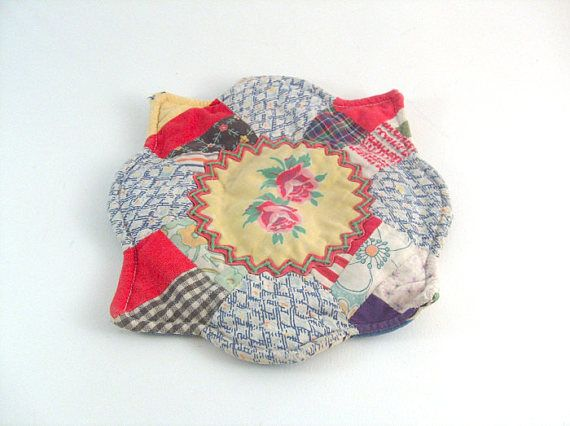 Vintage Pot Holder Hot Pad Feedsack Embroiered Farmhouse Primitive. Sweet vintage feedsack pot holder. Handmade vintage from the 1940s. The center of this flower shaped holder displays a sun shaped remnant fabric with two roses. The sun is finished with orange ric rac and embroidered with green thread. Reverse fabric is shown in photo 2. Measures 7 x 6 3/4. Good used vintage. There is wear at 2 of the corner points and along the border in a couple spots. One 1/4 tear on the re...