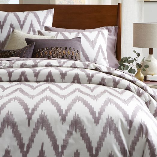 NEW COLOR! This graphic, large-scale interpretation of a woven ikat pattern simplifies the traditional ethnic motif down to its most basic and clear shapes, printing it in a light amethyst on stone-white cotton.