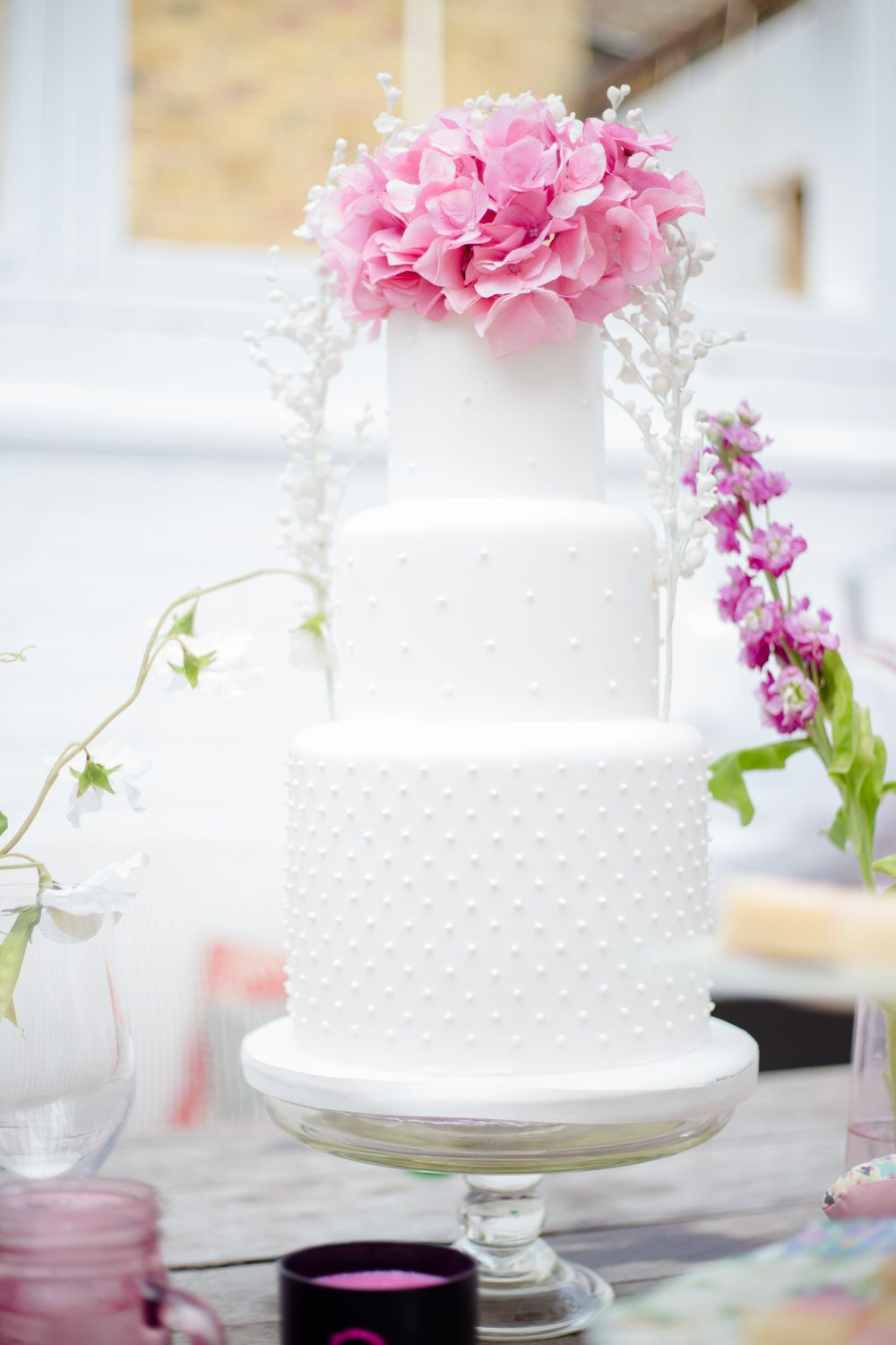 Three Tier White Wedding Cake topped with Pink Hydrangea Flower | Made To Order Bridesmaids Dresses From Award Winning Bridesmaid Dress Retailer Maids To Measure | Image by Claire Graham | http://www.rockmywedding.co.uk/maids-to-measure-sample-sale-august-2015/