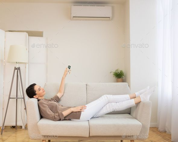 Young woman switching on air conditioning at her house by Prostockstudio Smart House Happy girl holding remote control relaxing under the air conditioner lying on couch c...
