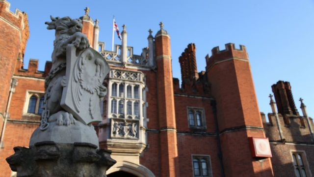 A beast statue in the foreground of the front entrance of Hampton Court.