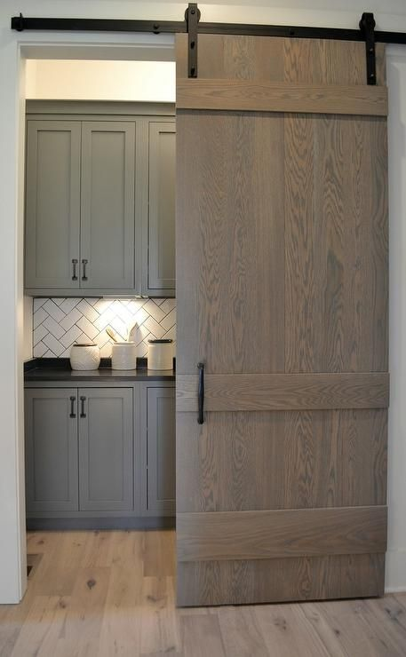 A Gray Wash Oak Barn Door On Oil Rubbed Bronze Rails Opens To Reveal A Gorgeous Laundry Room Cabin Kitchens