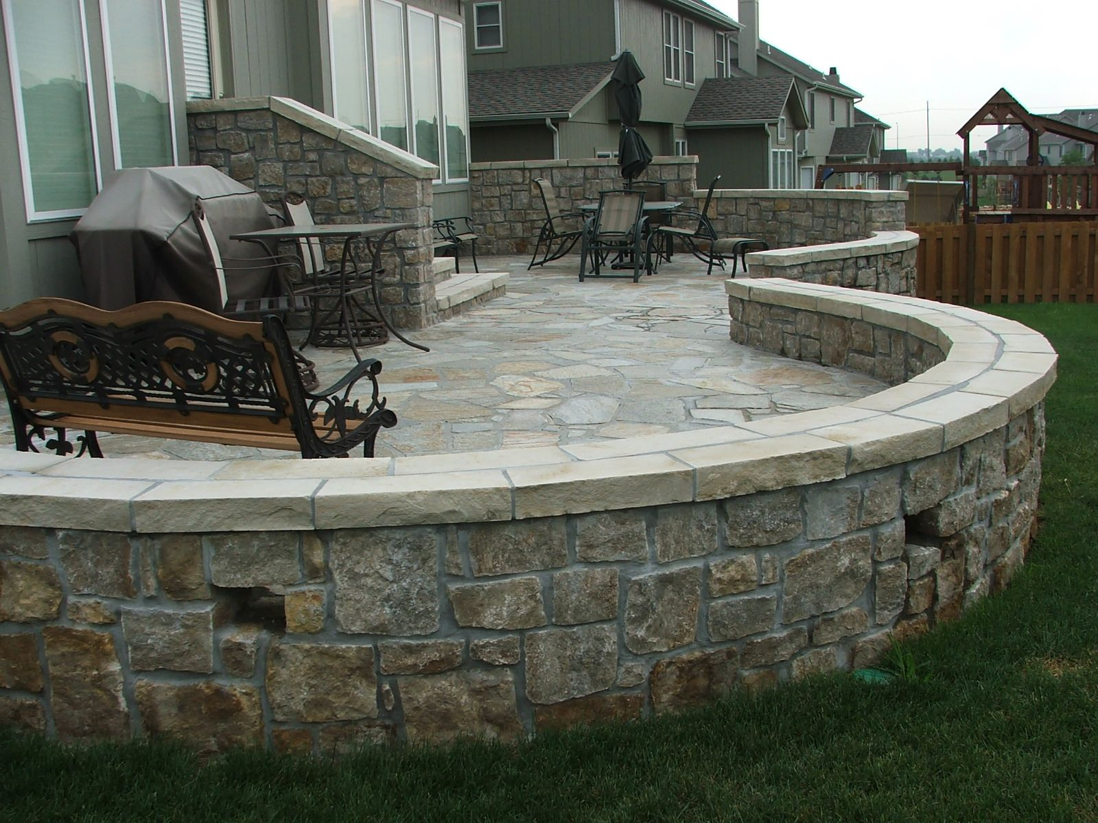 Natural stone patio with knee wall built by DW Elite Decks at